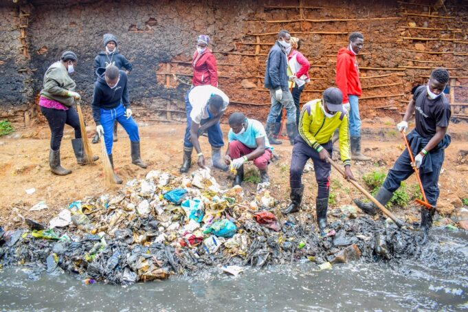 Volunteers clean a riverbank in Kibera
